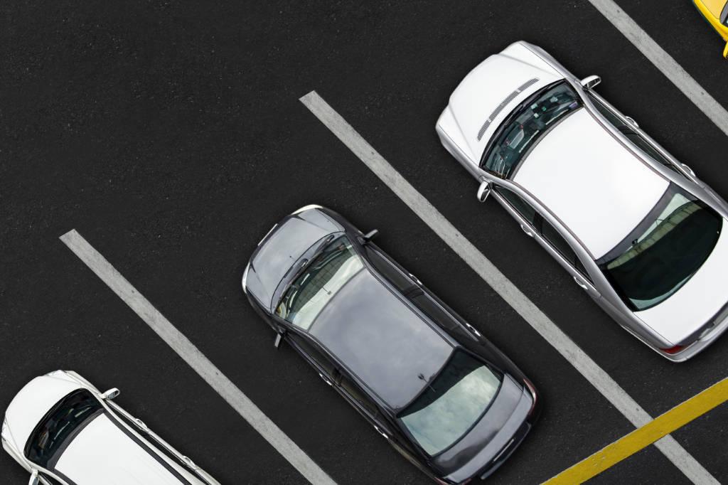 varios coches aparcados entre línea de parking